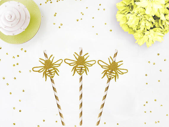 Gold striped straws topped with gold honey bees for a What will it bee? Gender reveal party