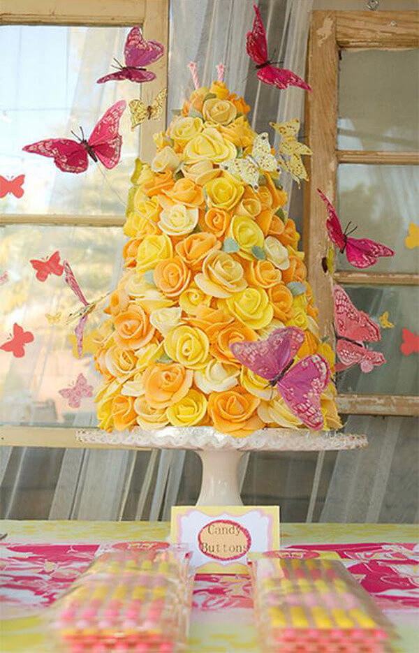 Cone shaped cake with yellow frosting roses and pink butterflies for an enchanted butterfly party.