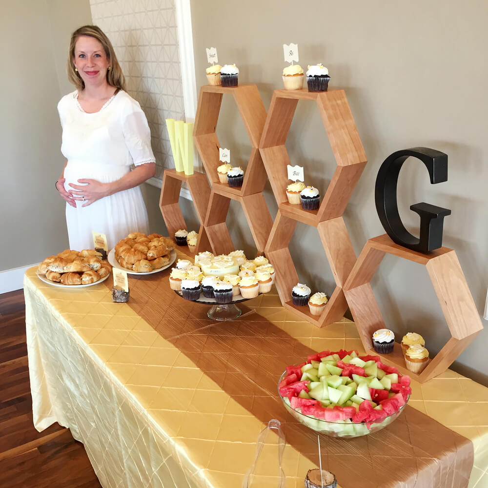 Mommy to bee standing next to food table at baby shower with honeycomb display
