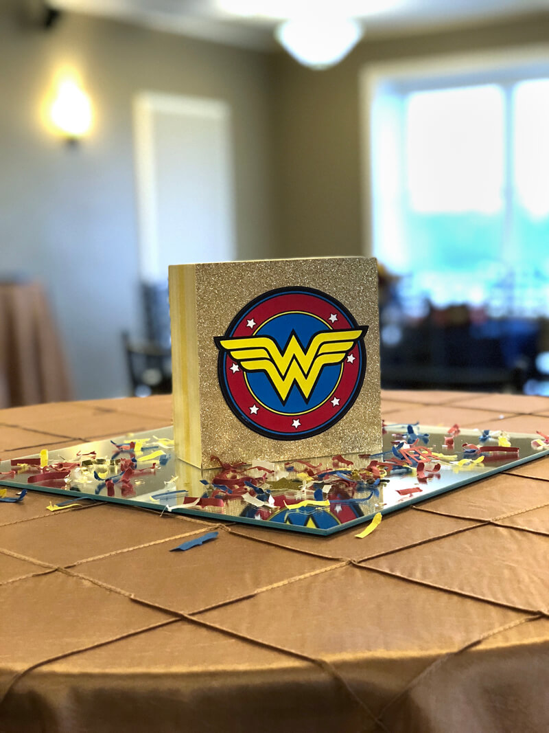 Mini Wonder Woman centerpiece on mirror tile with custom confetti for a Wonder Woman party