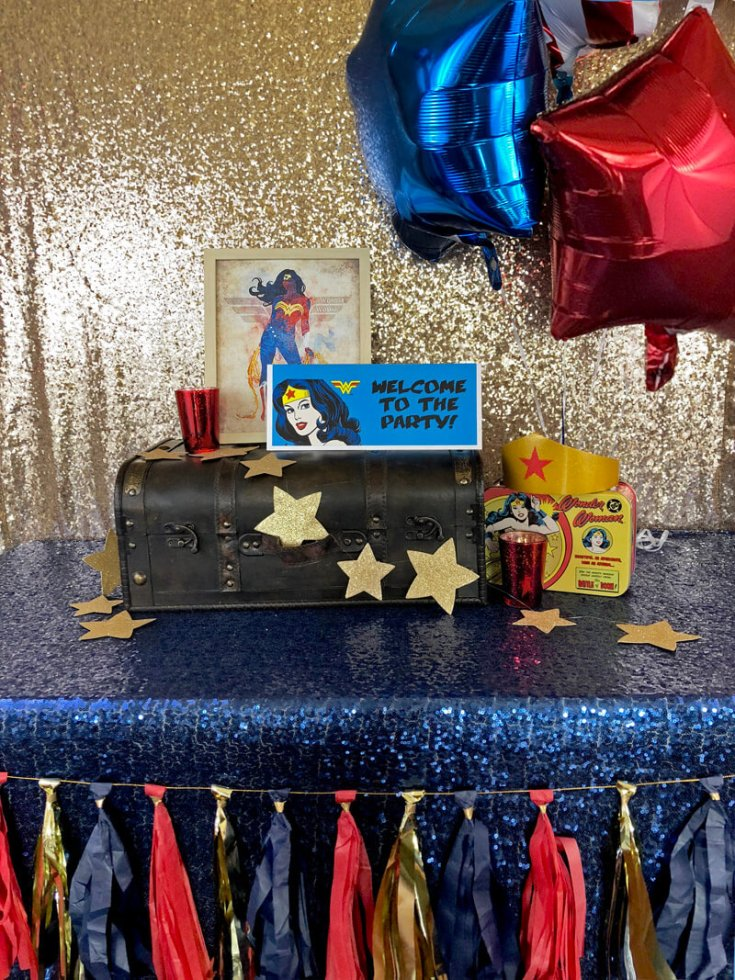 Suitcase on blue sequin tablecloth with gold stars and framed images for a Wonder Woman birthday party