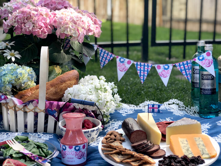 Meat and cheese tray, basket with flowers and bread, on blanket in grass for summer picnic party