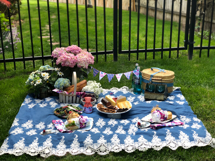 Charming summer picnic party spread on blanket in the grass