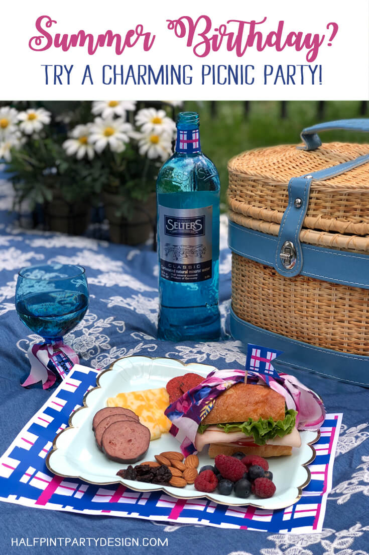 picnic basket, plate of food, glass, bottle of mineral water on blanket for a charming summer picnic party