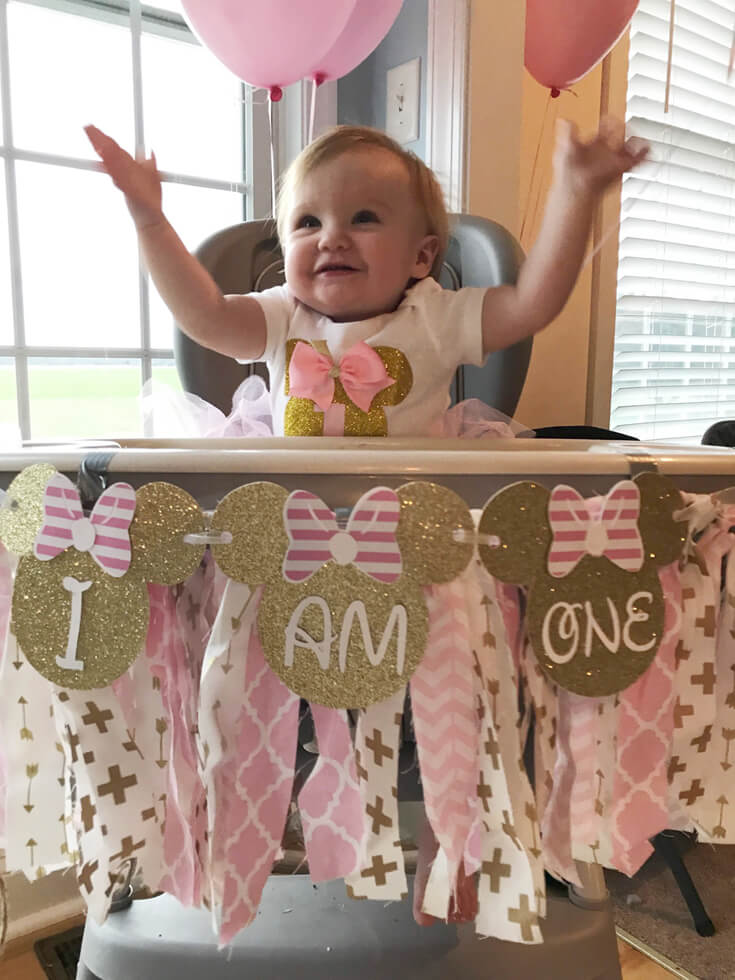 """Baby in high chair with banner """"I am one"""" for Minnie Mouse first birthday party"""