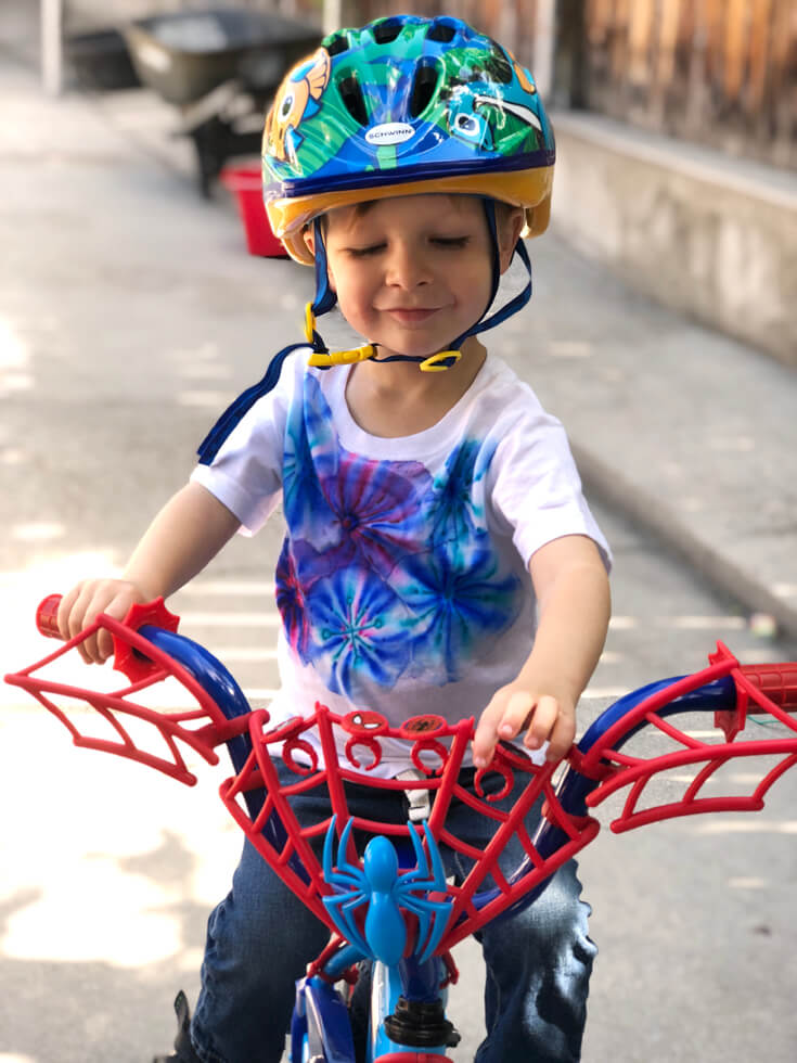 Boy riding bike with helmet on wearing sharpie t-shirt. A great kid's party craft.