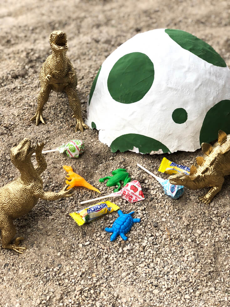 Broken DIY dino egg piñata with candy and toys surrounded by toy dinosaurs