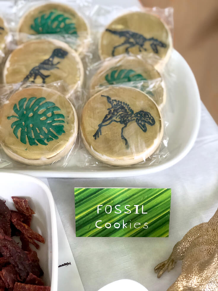 Monstera leaf and dinosaur fossil cookies for a dinosaur birthday party idea