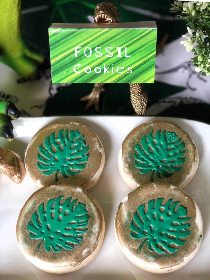 Monstera Leaf cookies at a T-rex graphic backdrop, balloon garland, and potted palm trees are a fabulous dinosaur birthday party