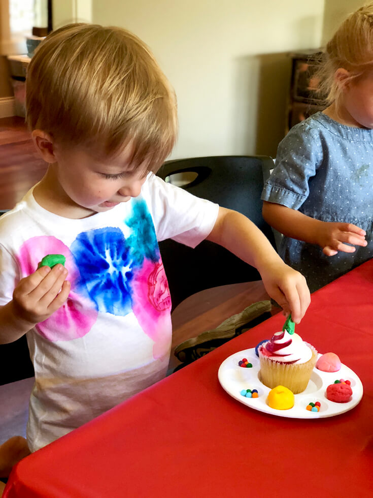 Child decorating a cupcake with sprinkles and edible playdough for a Play-doh birthday party