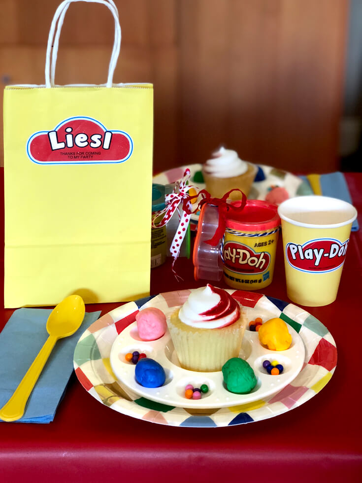 Colorful plate, cupcake, spinkles, and favor bag for a Play-doh birthday party