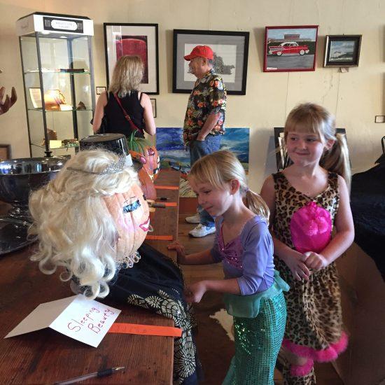 Children admire pumpkin carvings.