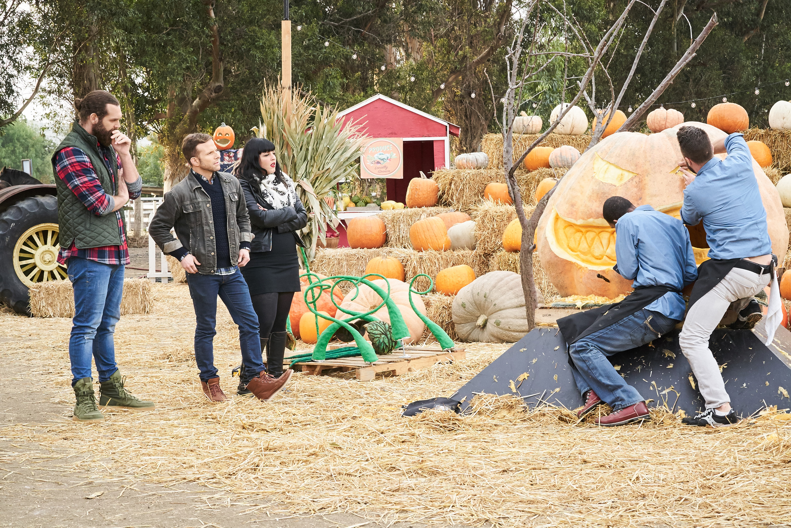 Host Harley Morenstein and judges Zac Young and Bianca Appice watch Chefs Adam Bierton and Stephen Baity of Team Deadly Intentions preparing their dish for the When Pumpkins Fight Back challenge, as seen on Food Network's 'Halloween Wars: Hayride of Horror', Season 1.