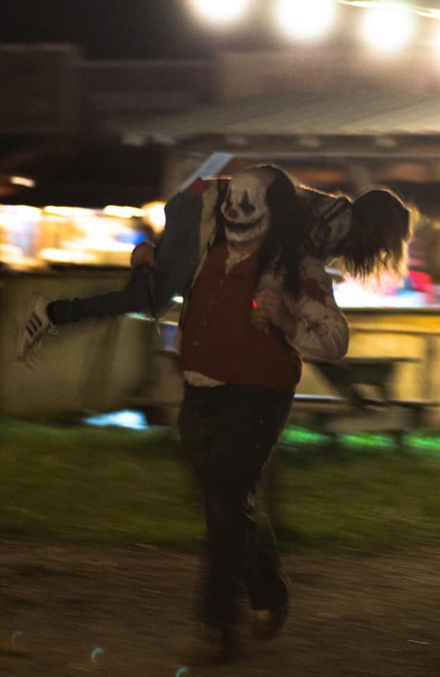 All Hallows Eve Terror Town Ohio Scariest Haunted House Clown Actor Carrying Patron