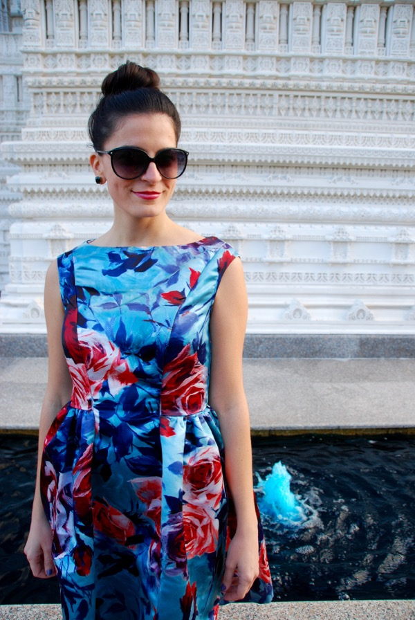 standing in a fall floral print dress with oversize black sunglasses