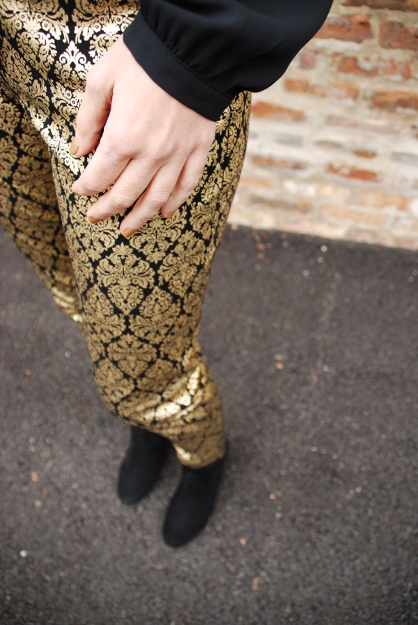 detail of gold brocade jacquard pants with black booties