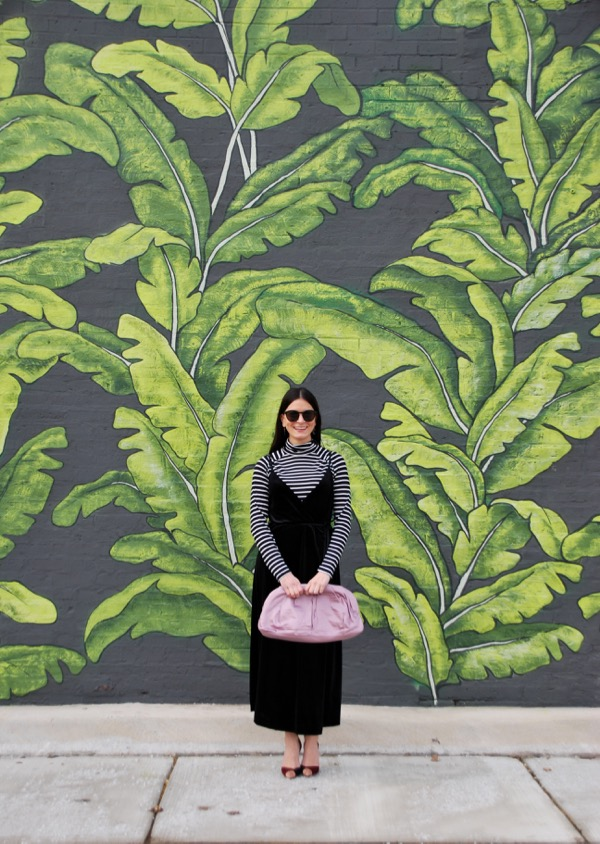 black velvet wrap dress in front of palm mural
