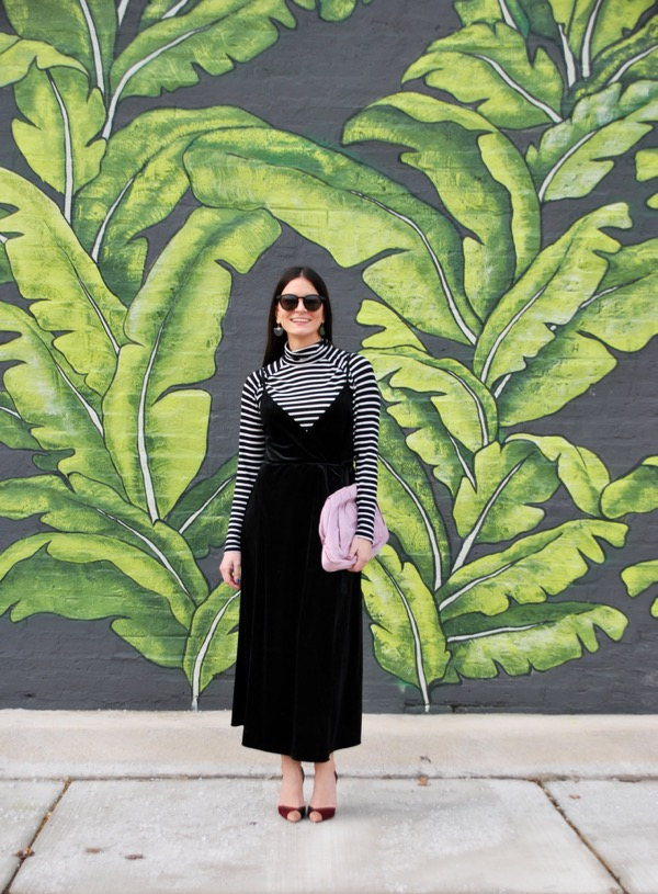 smiling in black velvet wrap dress with pink purse in front of palm mural