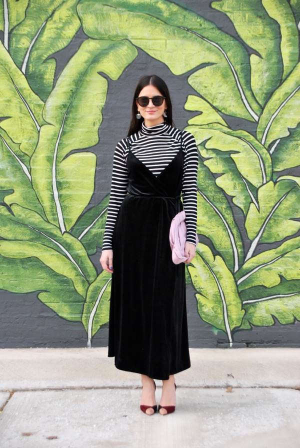 black velvet wrap dress with black and white stripe turtleneck and pink accessories in front of palm mural