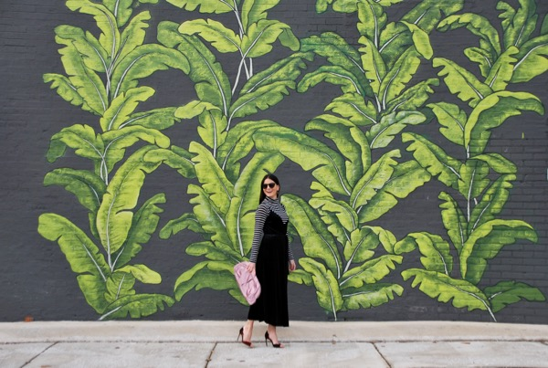 laughing in a black velvet wrap dress in front of palm mural