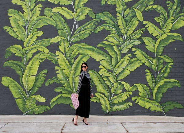 black velvet wrap dress in front of palm mural at eden chicago