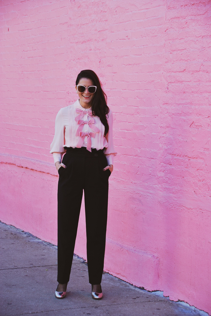 pink bow blouse with pearls and ruffle high waist black pants