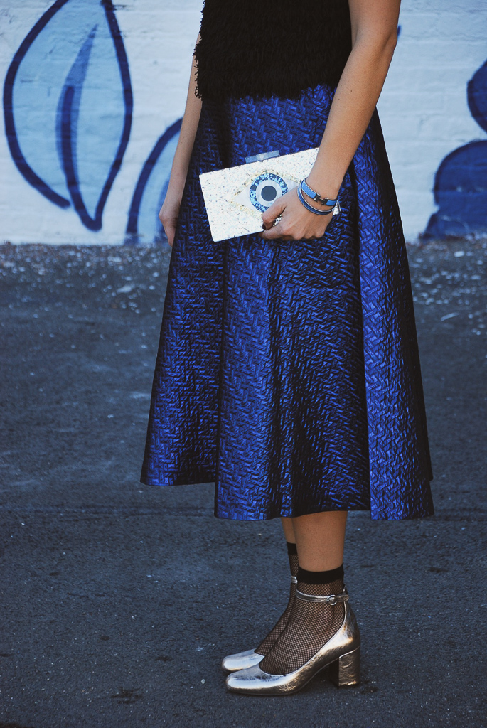 evil eye clutch, blue metallic midi skirt, and silver ankle strap round toe heels with fishnet ankle socks
