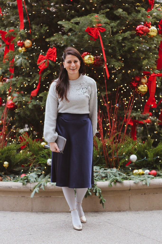 gray embellished sweater and blue satin skirt