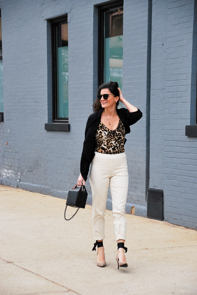 spring style: cream pants, leopard bodysuit, black blazer, black carryout bag
