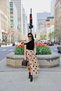 tan skirt with black polka dots and asymmetrical one shoulder black bodysuit