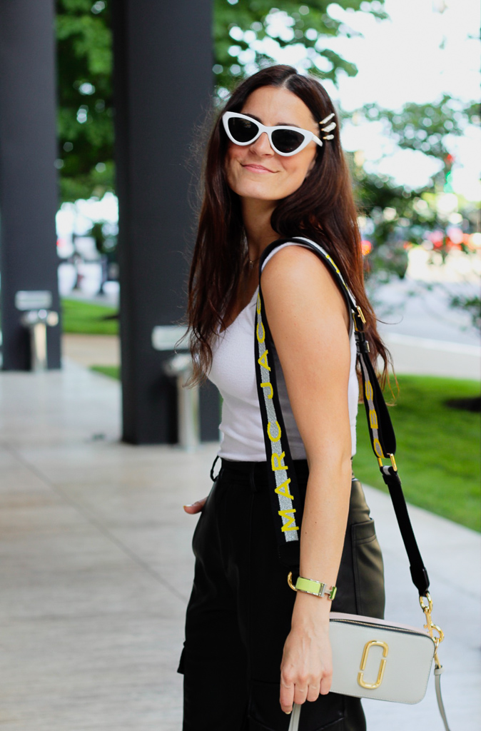 white cat eye sunglasses and camera bag with neon yellow and silver strap