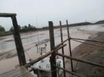 boat below dock, sandy river