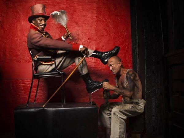 En man klädd en cirkusdirektör får sin sko putsad av en smutsig man utan tröja. Cirkusdirektören har sin ena fot ovanpå skoputsarens huvud.