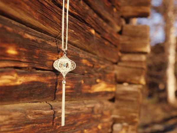 Ett av Rosa Taikons smycken hängd på timmervägg.
