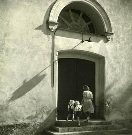 En kvinna och två barn går upp för en kyrktrappa under ett lunettfönster.