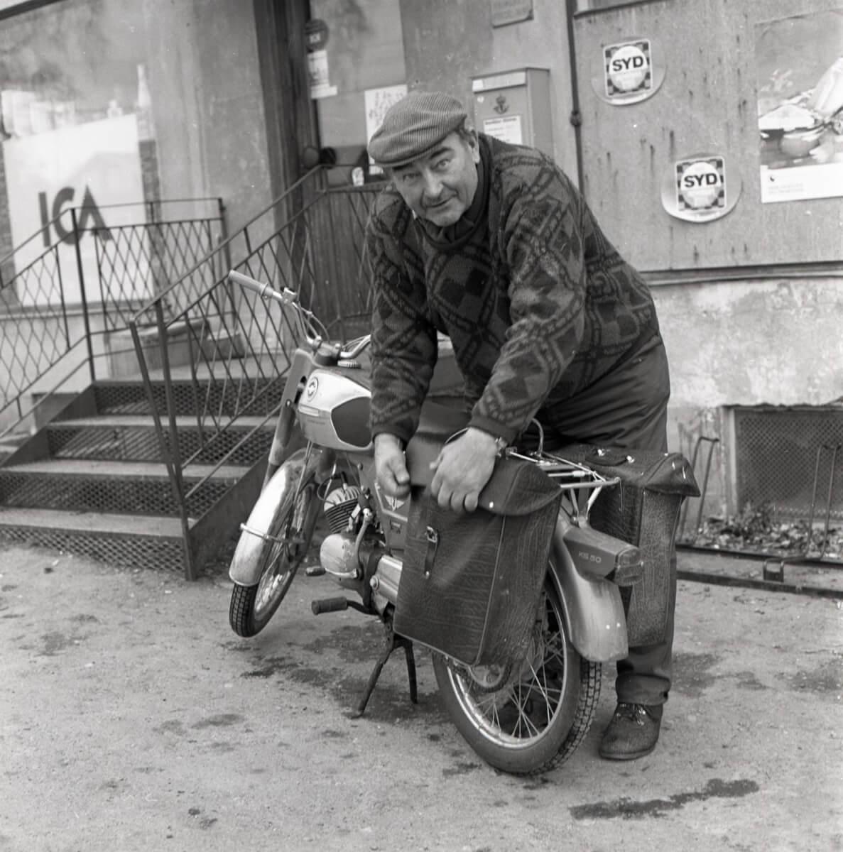 En man packar sina mopedväskor framför en ICA-butik. Han är klädd i sticketröja, han bär keps och grova kängor och plirar mot kameran. Butiken har reklam för Syd-apelsin på skyltfönstren. En betongbro leder in i affären, väggarna är släta och rappade.