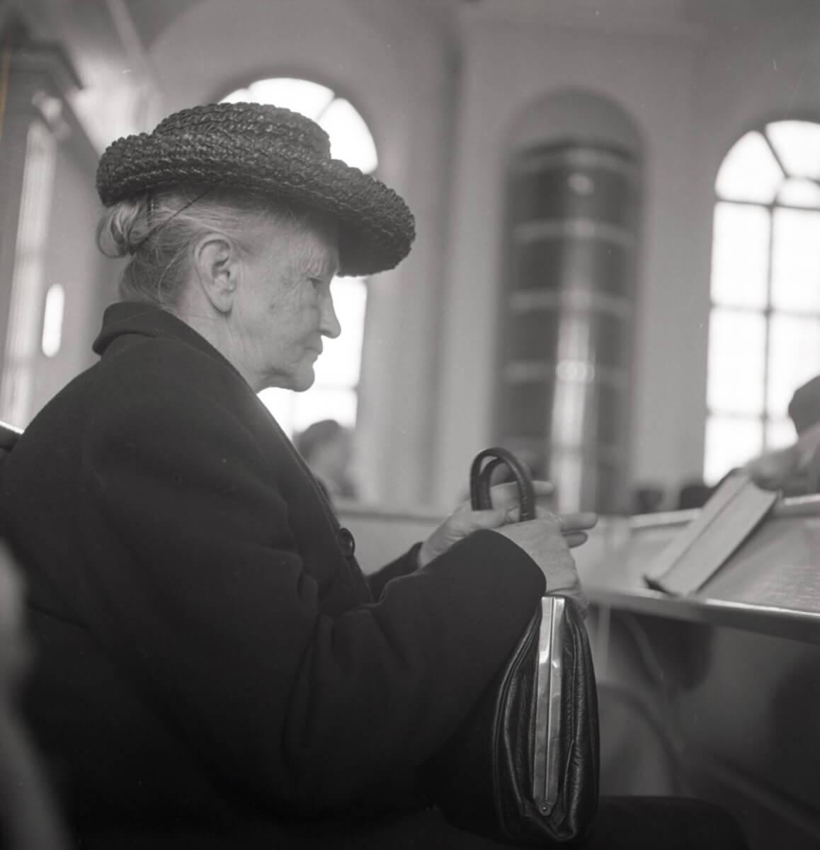 En kvinna sitter i en kyrkbänk.