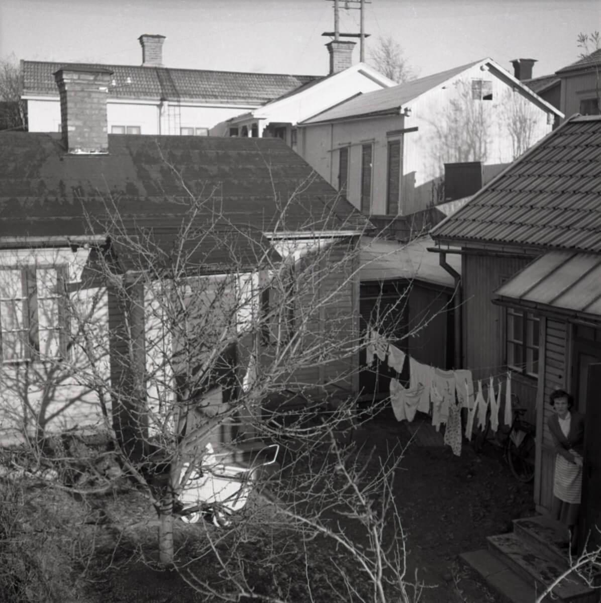 En stadsinnergård med upphängd tvätt på en tvättlina samt en kvinna som tittar ut genom en dörröppning.