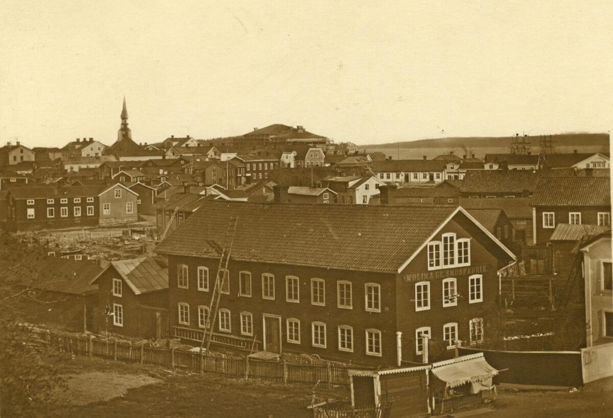 En mycket gammal bild av Hudiksvall med stora och små trähus som trängs längs gatorna. En stor träbyggnad i förgrunden har en skylt på gaveln där det står Molin & Co Snusfabrik. Man kan se Hudiksvallsfjärden och ett segelfartyg. Det gamla rådhuset sticker upp sin takspira till vänster. Bilden är tagen för 1879.