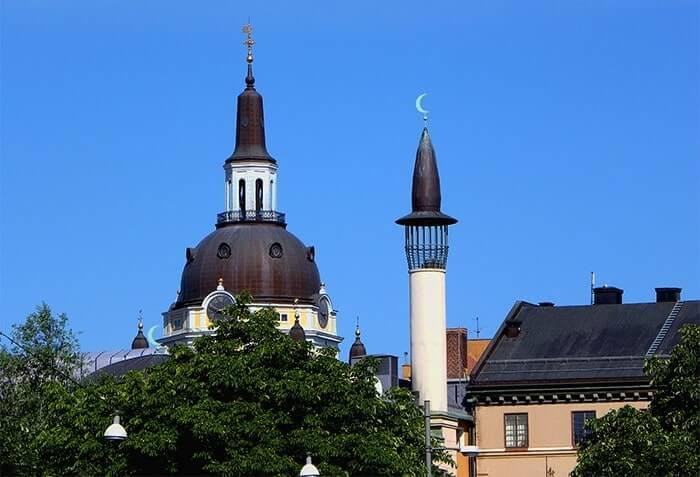 Stadsbild med tak prydda av religiösa symboler bakom ett grönt träd.