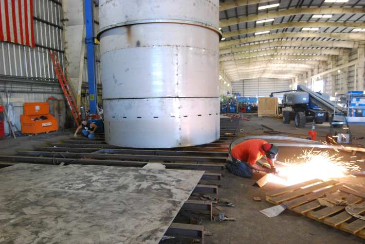 Man grinding near giant steel cylinder