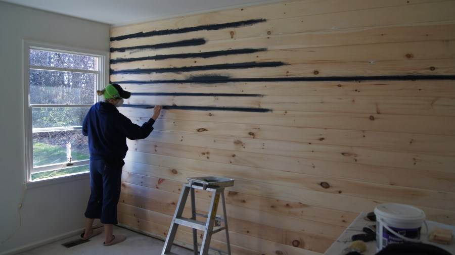 Shiplap vs  Nickel Gap  Making Your Budget Work For You     Hams at Home Painting navy blue paint on tongue and groove boards installed on wall
