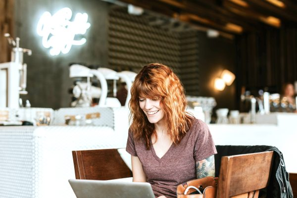 Blogging for Personal Brands - young woman sitting at a table in a coffee shop using a laptop and smiling
