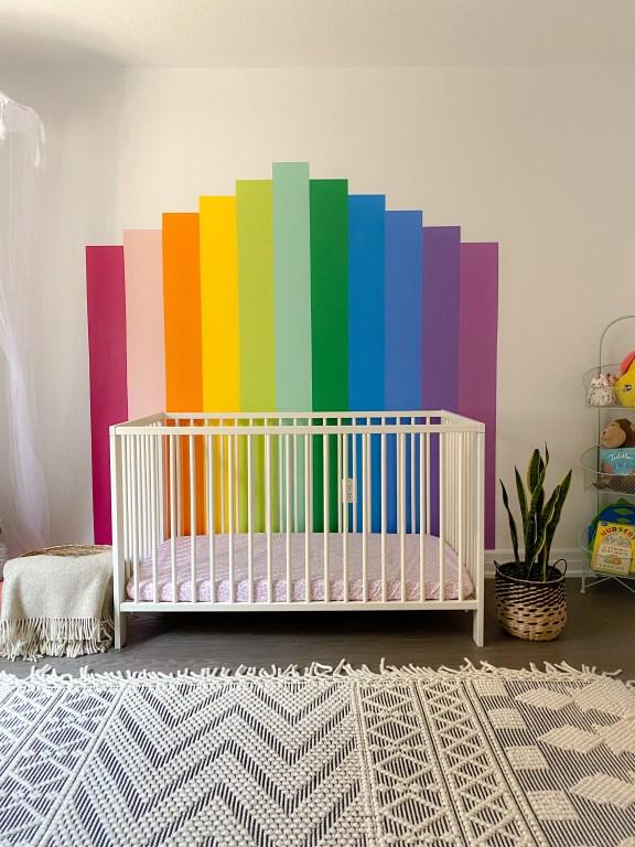 A rainbow mural on a wall with a white crib and blush crib