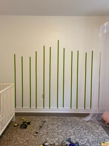 How to paint your rainbow mural, tape vertical stripes to the wall first.