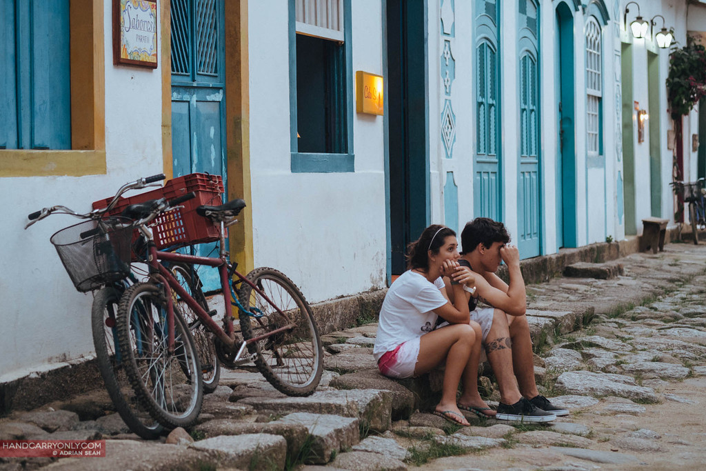 two kids sitting on sidewalk paraty brazil