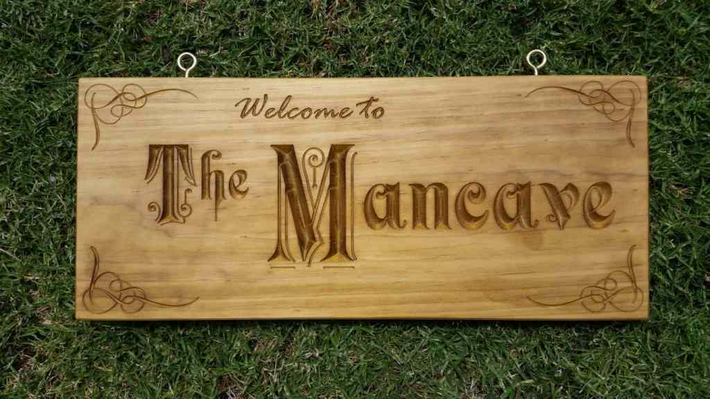 Wooden sign engraved with Welcome to The Mancave