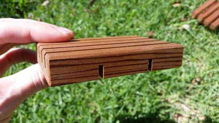 Close up photo of a cedar soap holder water drainage holes slots.