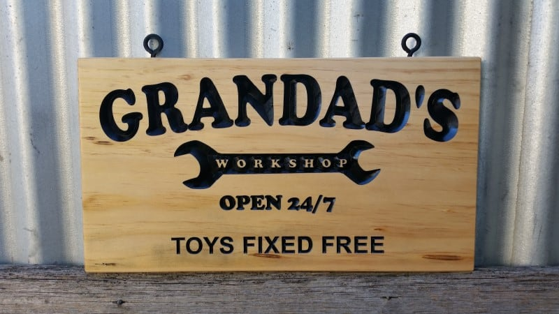 Pine sign with carved black lettering and black screw eyes for easy hanging. Reads 'Granddad's workshop open 24/7 toys fixed free
