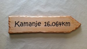 directional arrow sign made of wood reads kamanje 16,064km pointing right